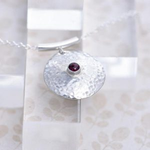 round silver pendant with Garnet in the centre made iana jewellery ips64