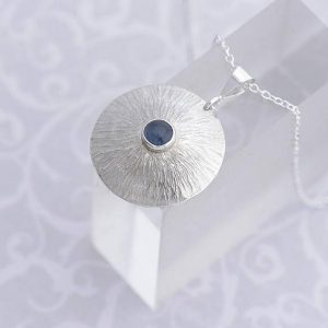 round silver pendant with sapphire in the centre by iana Jewellery